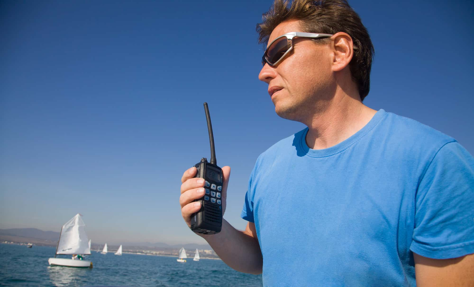 some man with walkie-talkie on the background of the sea with sails