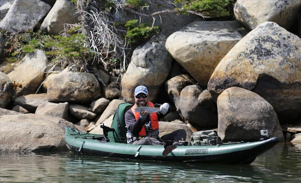 Man catching fish on inflatable kayak